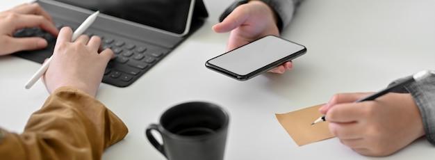 Bijgesneden schot van ondernemers werken op tablet en smartphone