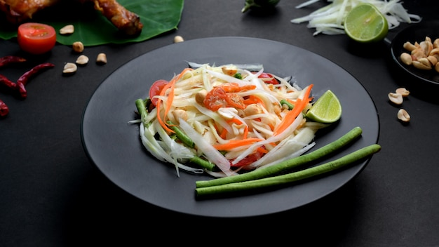 Bijgesneden schot van papaya salade, kip grill en ingrediënten op zwarte plaat