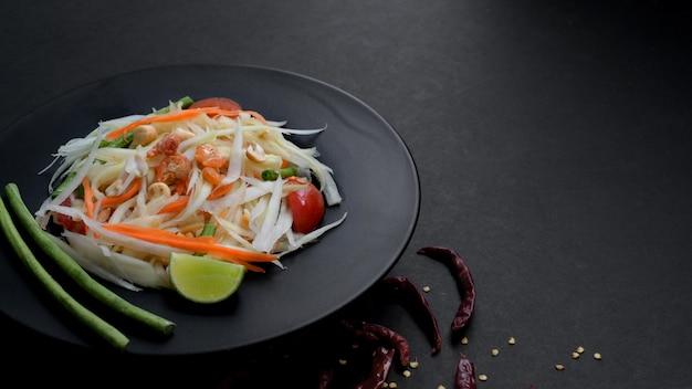 Bijgesneden schot van papaya salade of somtum op zwarte plaat