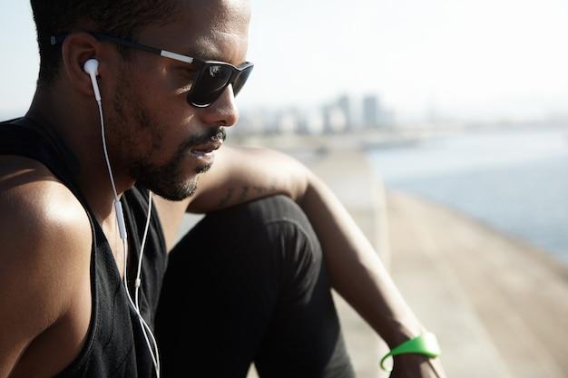 Bijgesneden schot van peinzende jonge knappe jogger in zonnebril zittend op de stenen trap, gekleed in zwarte sportkleding, op zoek verdrietig en serieus, luisteren naar muziek op zijn smartphone, rust