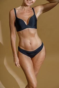 Bijgesneden schot van perfect fit lichaam van volwassen vrouw poseren half naakt in zwart ondergoed permanent in