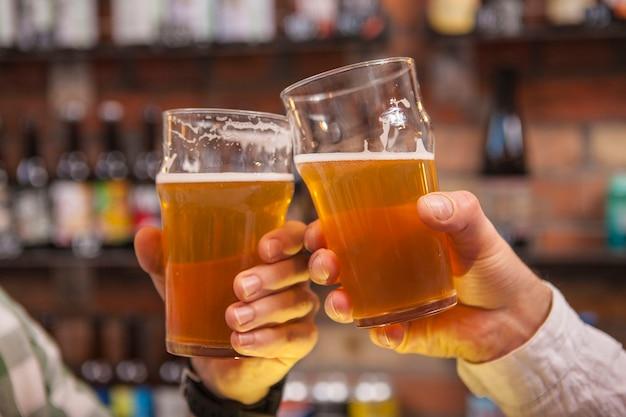 Bijgesneden schot van rammelende bierglazen van vrienden