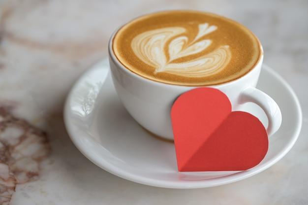 Bijgesneden schot van rood papier hart met koffie latte hart textuur op houten vloer.