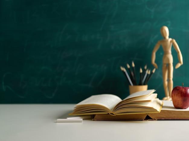 Bijgesneden schot van schoolelementen op witte tafel met kopie ruimte en schoolbord muur achtergrond
