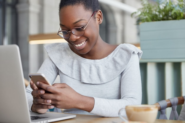 Bijgesneden schot van tevreden vrouwelijke copywriter leest positieve informatie op slimme telefoon, zit voor geopende laptopcomputer drinkt aromatische koffie.