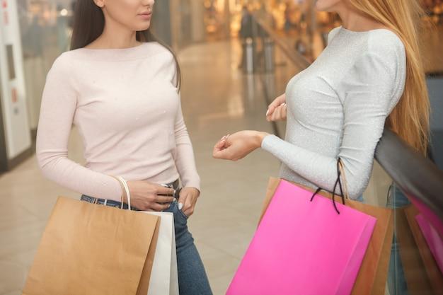 Bijgesneden schot van twee vrouwelijke klanten chatten in het winkelcentrum