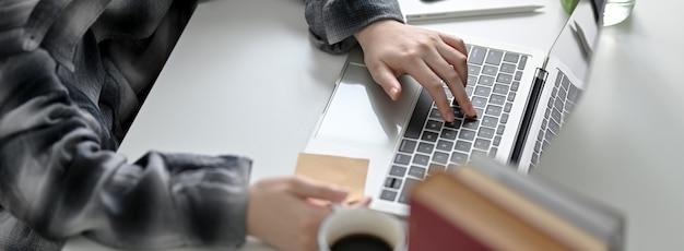 Bijgesneden schot van universiteitsstudent haar aanstaande examen met laptop, boeken en koffie op witte tafel voorbereiden