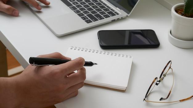Bijgesneden schot van universiteitsstudent korte notitie over notebook tijdens het lezen van tekst