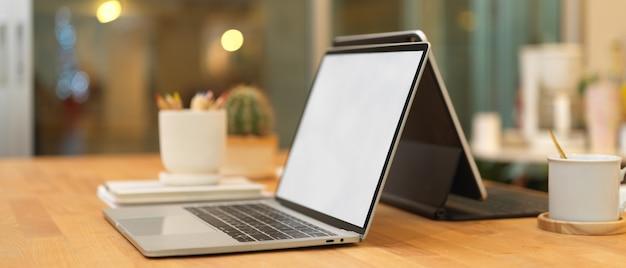 Bijgesneden schot van vergadertafel met twee laptops en kantoorbenodigdheden in kantoorruimte