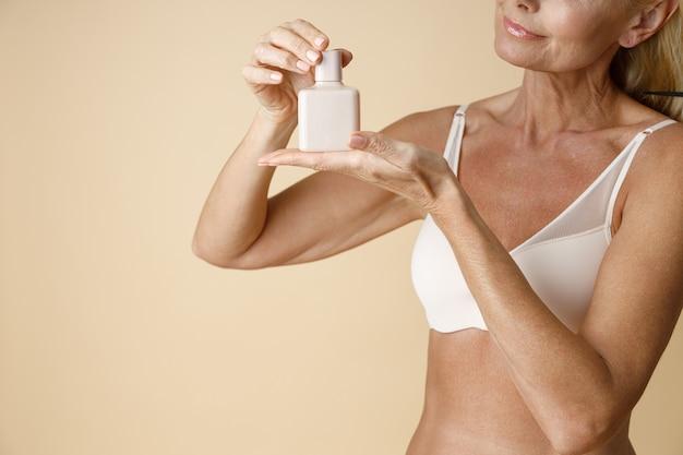 Bijgesneden schot van volwassen vrouw in ondergoed reclame vasthouden en kijken naar witte pot huidverzorging