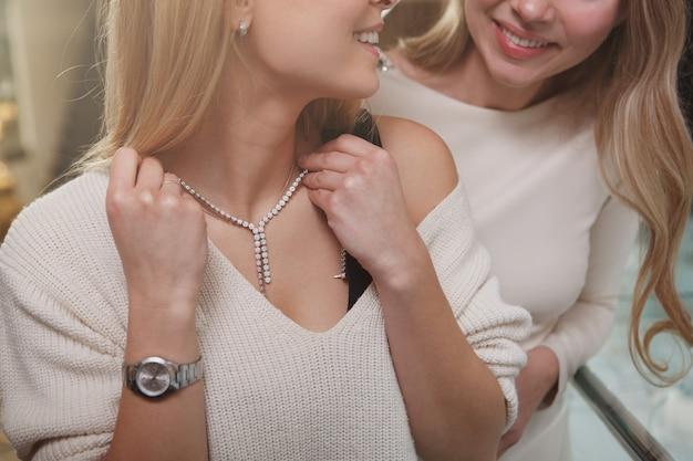 Bijgesneden schot van vrouw die lacht naar haar vriend, diamanten halsketting proberen