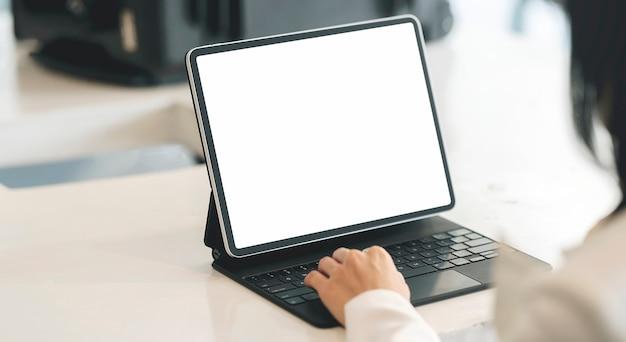 Bijgesneden schot van vrouw hand te typen op het toetsenbord van de tablet zittend aan tafel, leeg scherm voor grafisch ontwerp.