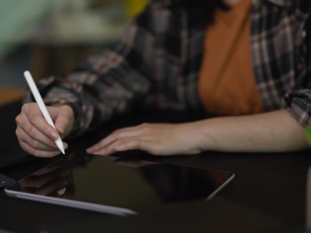 Bijgesneden schot van vrouw met behulp van digitale tablet met stylus op zwarte tafel in kantoorruimte