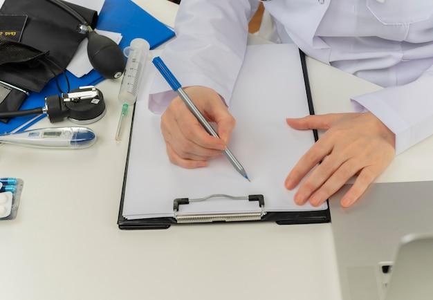 Bijgesneden schot van vrouwelijke arts handen werken bij bureau met medische hulpmiddelen en laptop recept schrijven op klembord