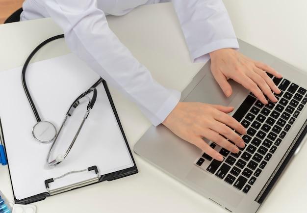 Bijgesneden schot van vrouwelijke arts handen werken met laptop aan balie met medische hulpmiddelen en klembord