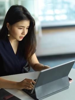 Bijgesneden schot van vrouwelijke beambte gericht op haar werk met digitale tablet in kantoorruimte