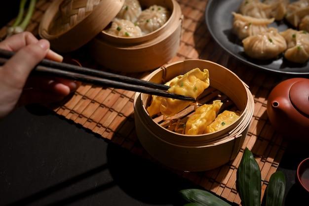 Bijgesneden schot van vrouwelijke hand met eetstokje dimsum dumplings plukken in bamboestoomboot op eettafel