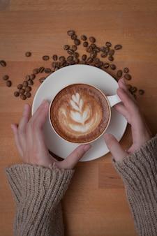 Bijgesneden schot van vrouwelijke handen met een kopje latte-koffie op houten werktafel versierd met koffiebonen