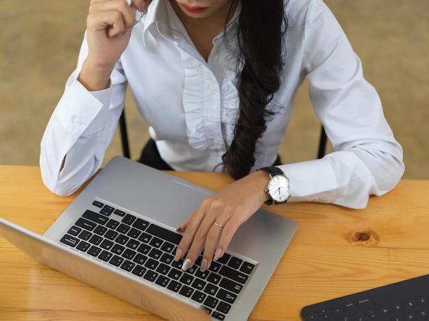 Bijgesneden schot van vrouwelijke kantoormedewerker die op laptop werkt tijdens het gesprek aan de telefoon op de werkplek