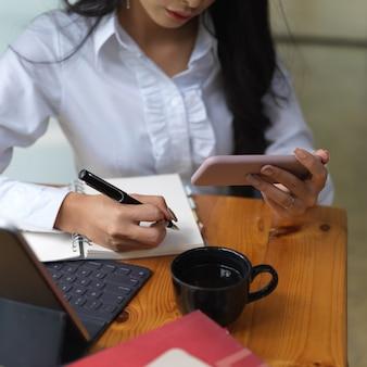 Bijgesneden schot van vrouwelijke nota nemen terwijl op zoek naar een idee op smartphone