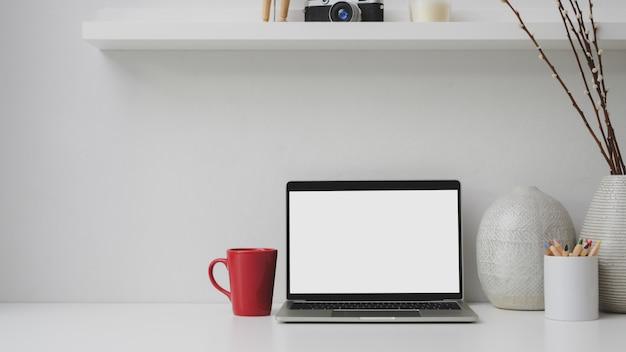 Bijgesneden schot van werkplek met leeg scherm laptop, rode koffiekopje, decoraties op wit bureau