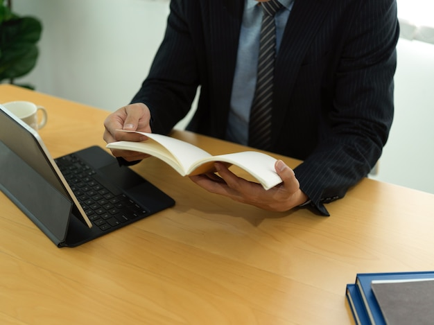 Bijgesneden schot van zakenman in zwart pak schema boek lezen zittend op de werkplek