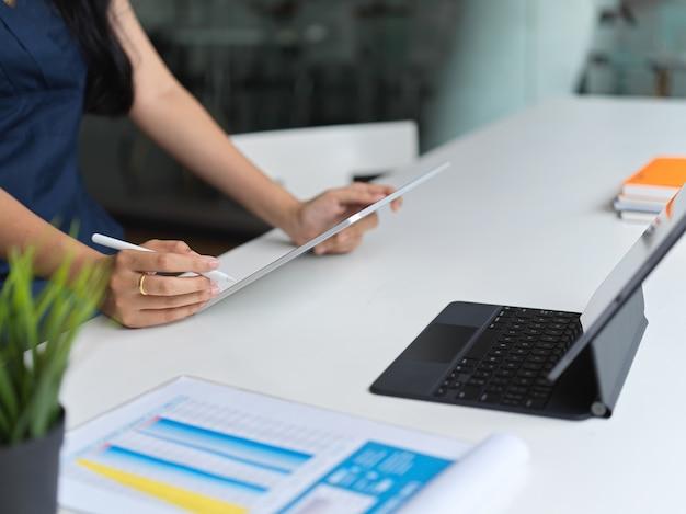 Bijgesneden schot van zakenvrouw bezig met haar project tijdens het gebruik van tablet in werkruimte