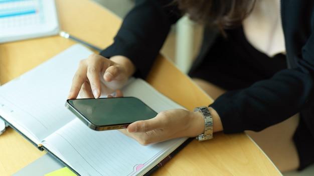 Bijgesneden schot van zakenvrouw met smartphone in haar hand op werkruimte met schemaboek