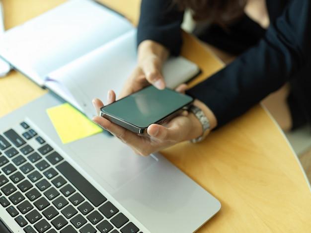 Bijgesneden schot van zakenvrouw smartphone op werkruimte met laptop en schema boek in kantoorruimte