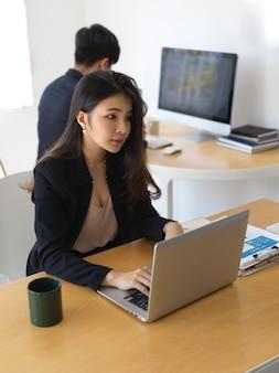 Bijgesneden schot van zakenvrouw werken met laptop en papierwerk in kantoorruimte met collega