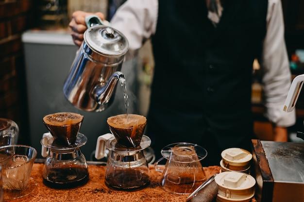 Bijgesneden shot barista koffie maker oude man druipend een kopje koffie op koffiepot met vintage toon.