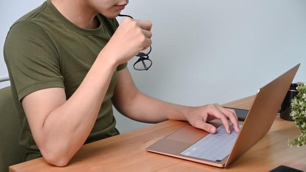 Bijgesneden shot man met bril en thuis werken met laptop.