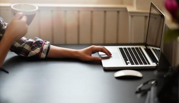 Bijgesneden shot van man koffie drinken en werken op laptop