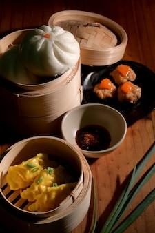 Bijgesneden shot van zelfgemaakte chinese knoedels, gestoomde gezouten eieren, varkensvleesballetjes en broodje