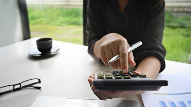 Bijgesneden shot vrouw berekening financiën gegevens op tafel.