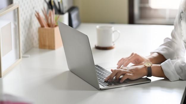 Bijgesneden shot vrouw handen met behulp van laptopcomputer op kantoor tafel.