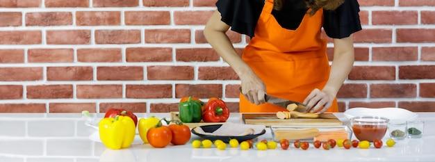 Bijgesneden shot vrouw in oranje schort staan voor bruine bakstenen muur van keuken en zorgvuldig snijden hotdog op kooktafel vol met verse tomaten, gezonde paprika en gerechten