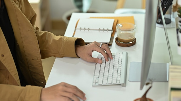 Bijgesneden shot zakenman werken met computer op kantoor aan huis.