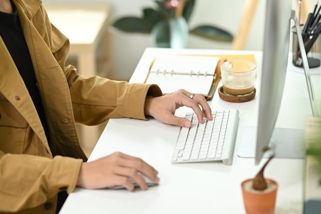 Bijgesneden shot zakenman zittend op een moderne werkplek en werken met de computer.