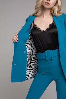 Bijgesneden stockfoto van onherkenbare slanke blonde vrouw in stijlvol blauw pak met zebra voering en zwarte lingerie top. anoniem blond model dat haar stijlvolle look demonstreert. bijgesneden studiofoto.