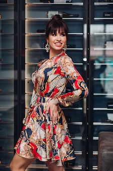 Bijgesneden stockfoto van onherkenbare slanke vrouw die luxe zijden cocktailjurk met patroon draagt. ze poseert in een restaurant.