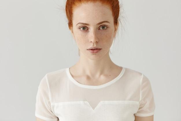 Bijgesneden studio-opname van mooie blanke vrouw met rood haar en sproeten