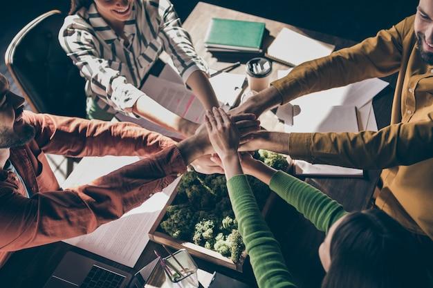 Bijgesneden top boven hoge hoekmening van vier mooie vrolijke professionele zakenlui dragen casual formalwear handen in elkaar zetten over bureau