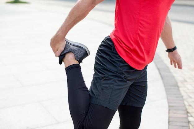 Bijgesneden uitzicht van de mens stretching leg outdoors