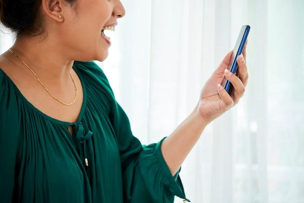 Bijgesneden van opgewonden gelukkige jonge vrouw met smartphone in handen die videogesprek voert met haar vriend of familielid