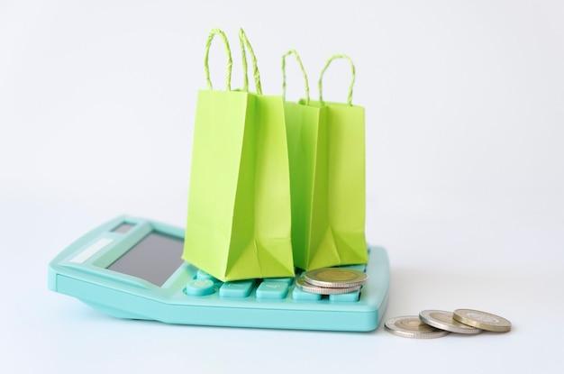 Bijgesneden van persoon met behulp van rekenmachine door munten en kleine dozen op tafel