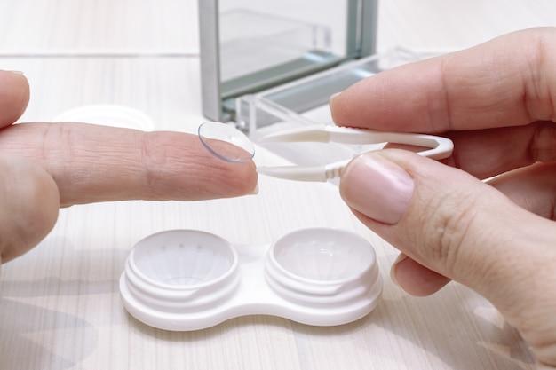 Bijgesneden vrouwelijke handen nemen contactlenzen uit een container