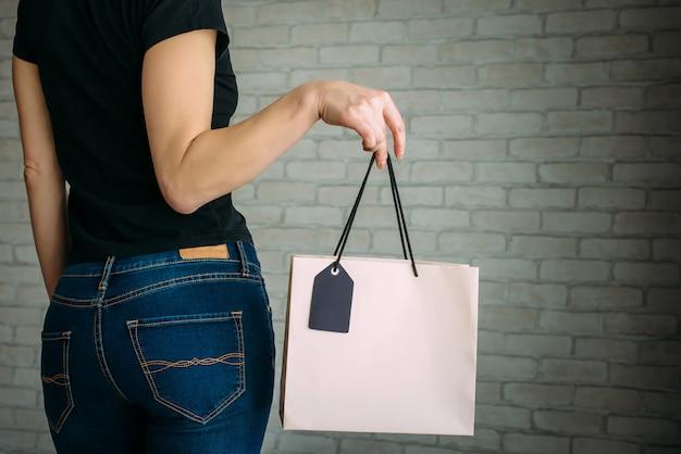 Bijgesneden weergave sexy vrouw in denim met papieren zak met tag in haar hand tegen een witte bakstenen muur in het winkelcentrum. kopieer ruimte. black friday-verkoopconcept.