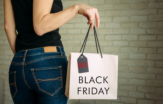 Bijgesneden weergave sexy vrouw in denim met papieren zak met tag in haar hand tegen een witte bakstenen muur in het winkelcentrum