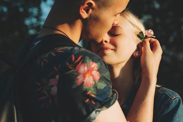 Bijgesneden weergave van aantrekkelijke man die teder sierlijke roze bloem aan haar vastmaakt achter het oor van mooie jonge blonde vrouw die hem knuffelt met gesloten ogen